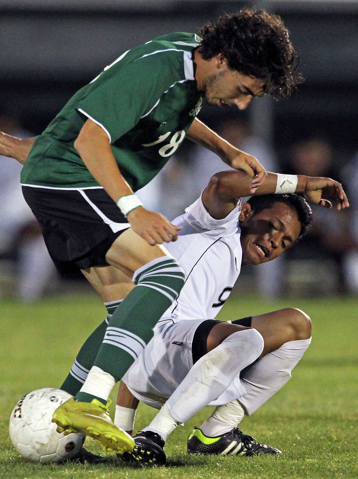 Reagan's Alex Galvan (left) and Southwest's Guillermo Lazcano fight for possession as the Dragons take on the Rattlers in the playoffs at Blossom Soccer Stadium on Tuesday, April 10, 2012.