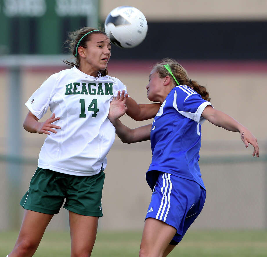 Reagan's Caitlin Owen wins a header battle against MacArthur's Catherine Sharp as the Brahmas take on the Rattlers in the playoffs at Blossom Soccer Stadium on Tuesday, April 10, 2012. Photo: TOM REEL, San Antonio Express-News / San Antonio Express-News