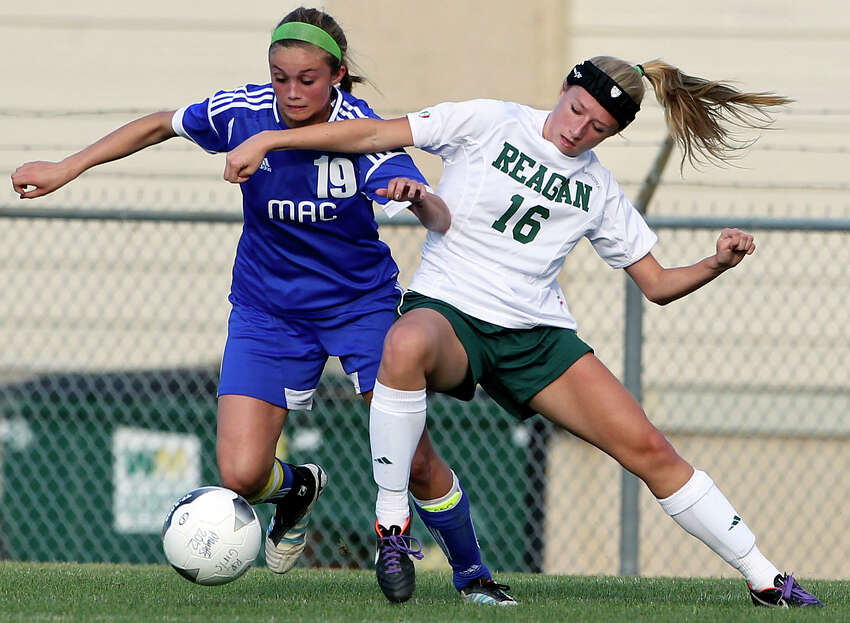 MacArthur's Catherine Sharp battles Reagan's Lisa Zagorski as the Brahmas take on the Rattlers in the playoffs at Blossom Soccer Stadium on Tuesday, April 10, 2012.