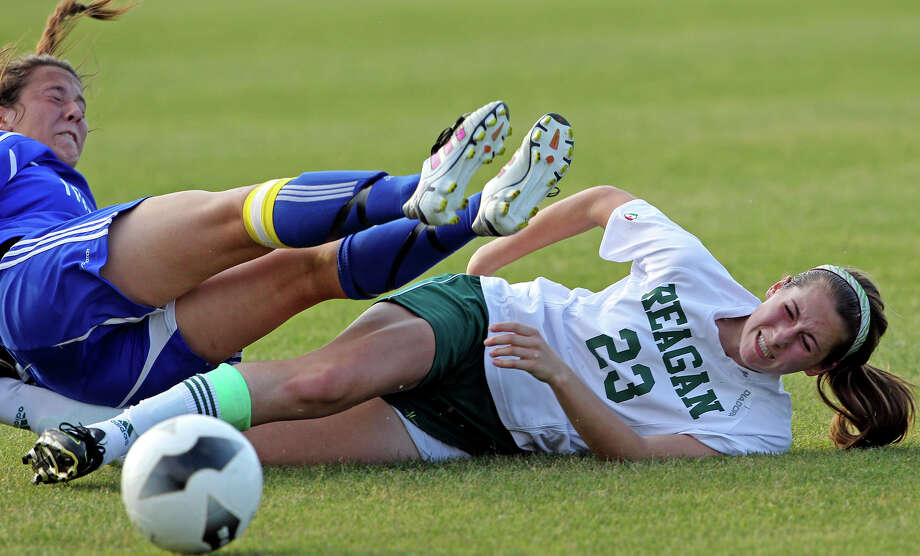 MacArthur's Courtney Bertholf tumbles over Reagan's Ashley Long as they scramble for a loose ball as the Brahmas take on the Rattlers in the playoffs at Blossom Soccer Stadium on Tuesday, April 10, 2012. Photo: TOM REEL, San Antonio Express-News / San Antonio Express-News