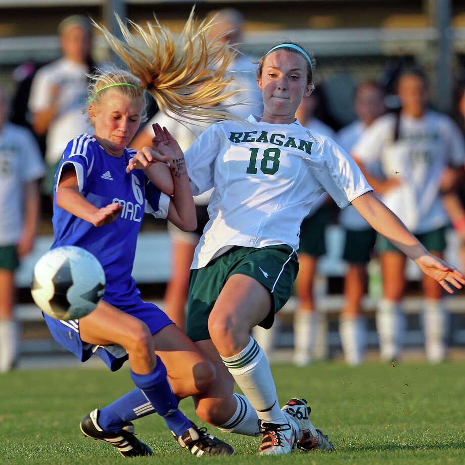 MacArthur's Sydney Joyce and Reagan's Carly Hankins crash into each other contending for the ball as the Brahmas take on the Rattlers in the playoffs at Blossom Soccer Stadium on Tuesday, April 10, 2012. Photo: TOM REEL, San Antonio Express-News / San Antonio Express-News