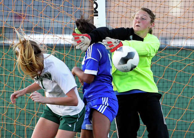 MacArthur goalkeeper Lauren Majek makes sure the ball is swatted away from Reagan's Taryn Sherman and teammate Alexis Brown   as the Brahmas take on the Rattlers in the playoffs at Blossom Soccer Stadium on Tuesday, April 10, 2012. Photo: TOM REEL, San Antonio Express-News / San Antonio Express-News