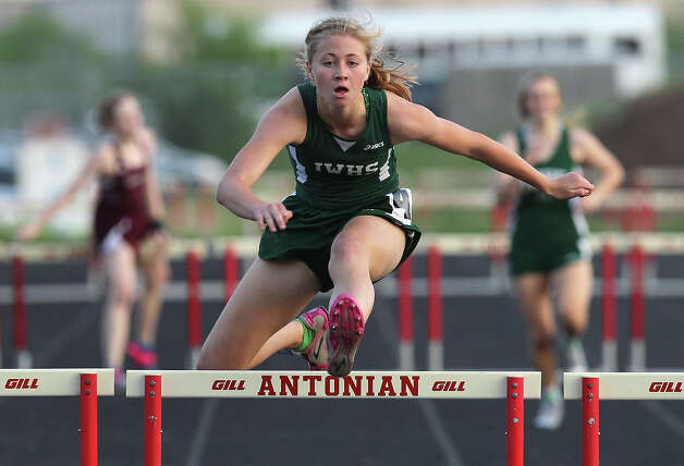 Incarnate Word High School's Emily Phillips clears the final obstacle to finish first in the 300-meter hurdles at the TAPPS 2-5A track meet championships at Antonian High School on Tuesday, April 10, 2012. Photo: Kin Man Hui, San Antonio Express-News / ©2012 San Antonio Express-News