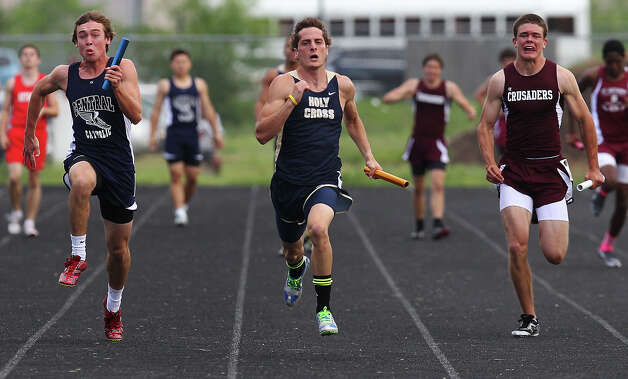 Sam Romero of Holy Cross (center) takes first for his relay team in the 4x100 meter relays by outrunning Central Catholic's Walker Sinclair (left) and Austin St. Michael's Carl Schiro (right) at the TAPPS 2-5A track meet championships at Antonian High School on Tuesday, April 10, 2012. Photo: Kin Man Hui, San Antonio Express-News / ©2012 San Antonio Express-News
