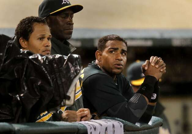 Oakland's Yoenis Cespedes, (right) watches from the dugout, as the Oakland Athletics take on the Kansas City Royals in major league baseball action at the O.Co Coliseum on Tuesday April 10, 2012, in Oakland, Ca. Photo: Michael Macor, The Chronicle