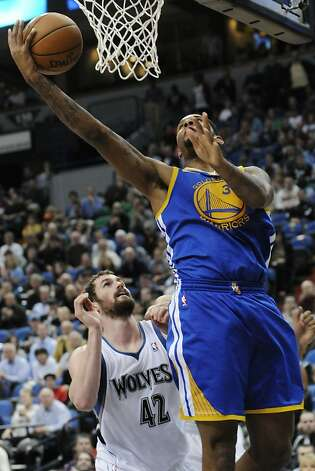 Golden State Warriors' Jeremy Tyler shoots a layup past Minnesota Timberwolves' Kevin Love in the second half of an NBA basketball game, Wednesday, April 4, 2012, in Minneapolis. The Warriors won 97-94. Photo: Jim Mone, Associated Press