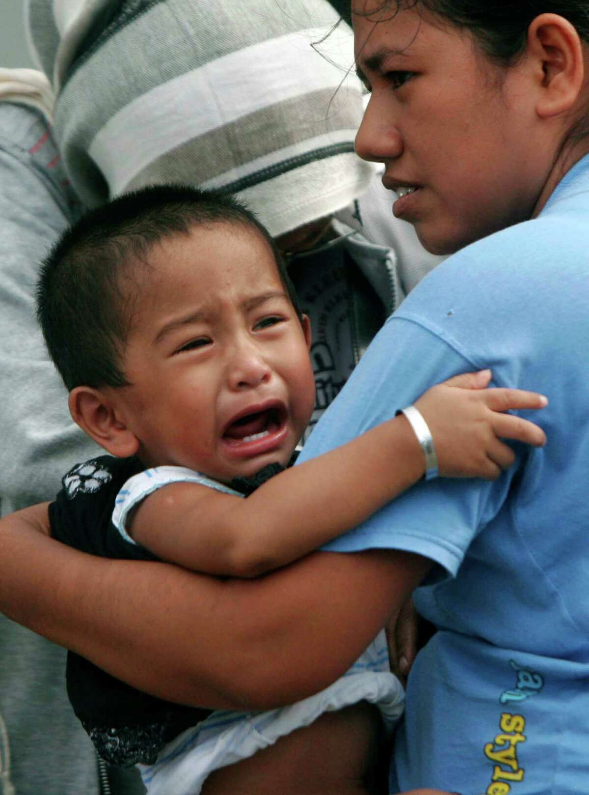 A boy cries as he is carried by his mother as they evacuate to higher ground after a strong earthquake was felt in Banda Aceh, Aceh province, Sumatra island, Indonesia, Wednesday, April 11, 2012. Two massive earthquakes triggered back-to-back tsunami warnings for Indonesia on Wednesday, sending panicked residents fleeing to high ground in cars and on the backs of motorcycles. There were no signs of deadly waves, however, or serious damage, and a watch for much of the Indian Ocean was lifted after a few hours.