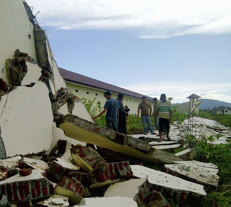 People look at walls damaged by a strong earthquake at a prison in Aceh province in Indonesia, Wednesday, April 11, 2012. Two massive earthquakes triggered back-to-back tsunami warnings for Indonesia on Wednesday, sending panicked residents fleeing to high ground in cars and on the backs of motorcycles. No deadly waves or serious damage resulted, and a watch for much of the Indian Ocean was lifted after a few hours. (AP Photo/Kyodo News) JAPAN OUT, MANDATORY CREDIT, NO LICENSING IN CHINA, HONG KONG, JAPAN, SOUTH KOREA AND FRANCE Photo: AP / Kyodo News