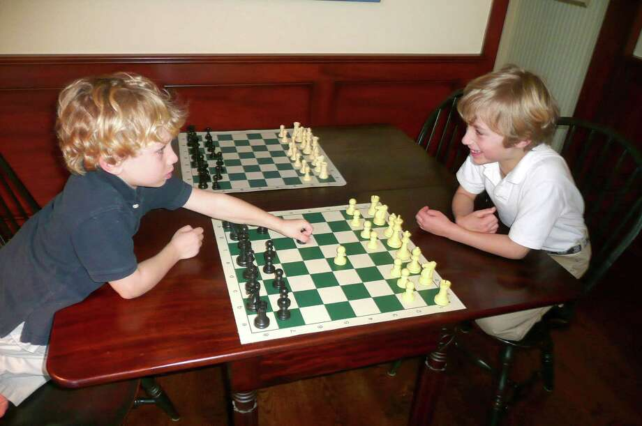 Brothers Thomas Ewald, left, and William Ewald, right, each took a title at the Connecticut Scholastic Chess Championship, which was held recently in New Haven. Thomas, 6, won the kindergarten championship and William, 7, won the first-grade title. The two brothers are students of chess teacher and Greenwich resident Rich Jackson. Photo: Anne W. Semmes