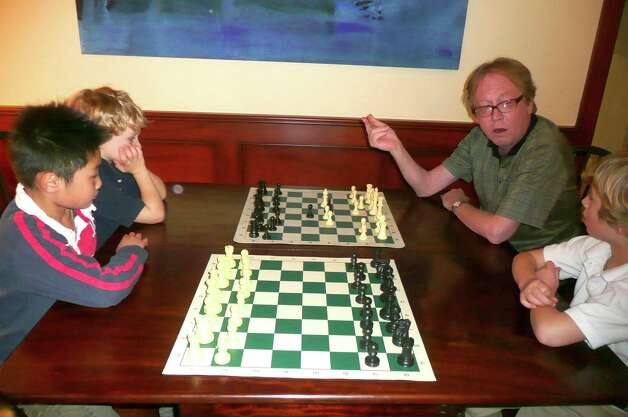 "William and Thomas Ewald take lessons from professional chess teacher and Greenwich resident Rich Jackson, right. Here, Jackson instructs the Ewald brothers and another state champion, Dennis Li, of Greenwich, who won the fourth-grade title this year. William Ewald says of his coach, ""He is very smart, good at teaching and has a good memory."" Photo: Anne W. Semmes"