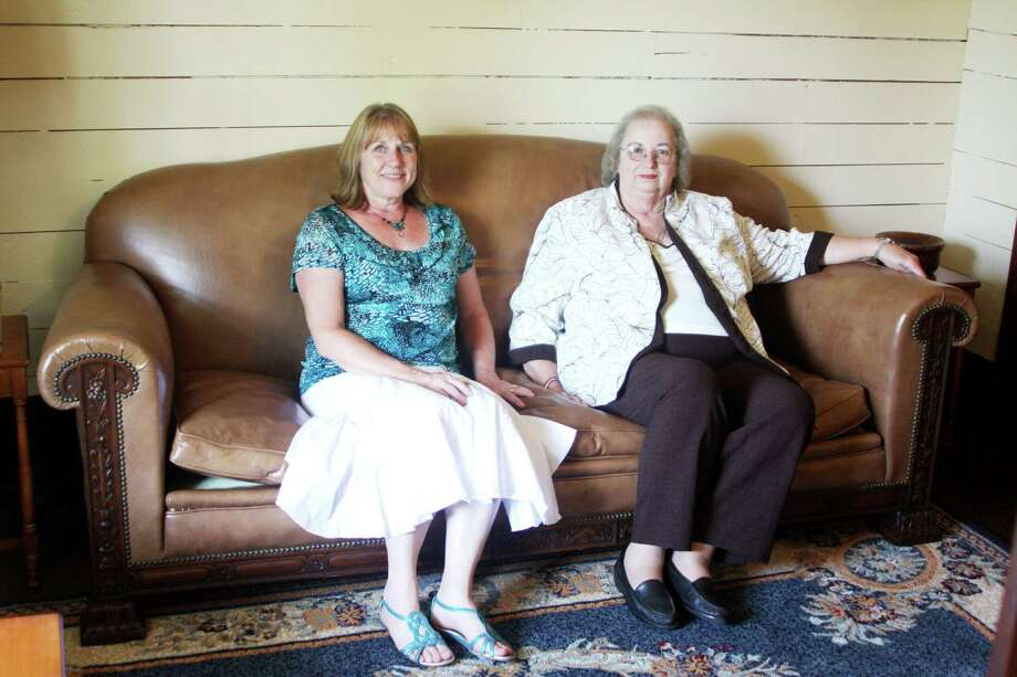 Rose Hall, left, and Elaine Allums, right, sit on a hand crafted leather sofa in the Kirby-Hill House. The sofa is part of a collection of John Henry Kirby's personal office furniture donated to the Kirby-Hill House by the Stephen F. Austin College of Forestry. Photo: David Lisenby, HCN_Kirby