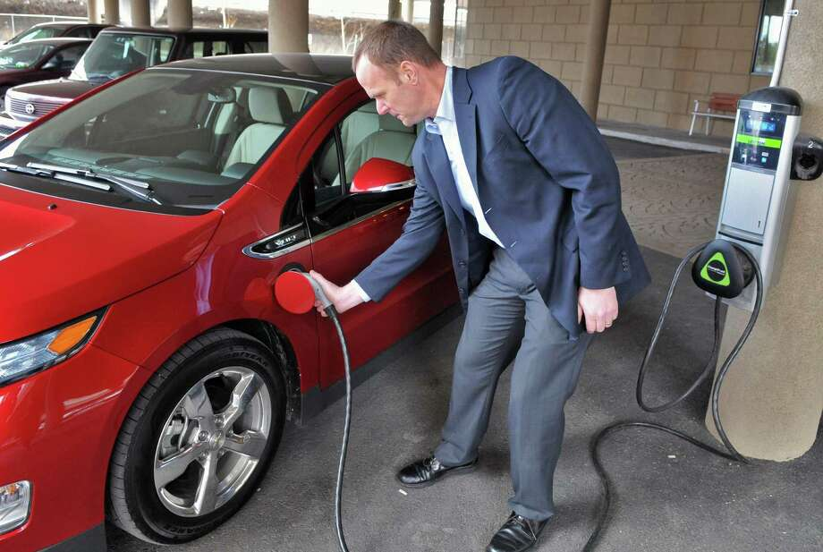 General Motor's Stephen Marlin demonstrates using a public recharging station to charge up a Chevy Volt from the 2012 Albany Auto Show Times Union Center in Albany March 9, 2012. New Canaan will get a similar charging station installed in the Morse Court Parking lot. (John Carl D'Annibale / Times Union) Photo: John Carl D'Annibale, Albany Times Union / ONLINE_YES