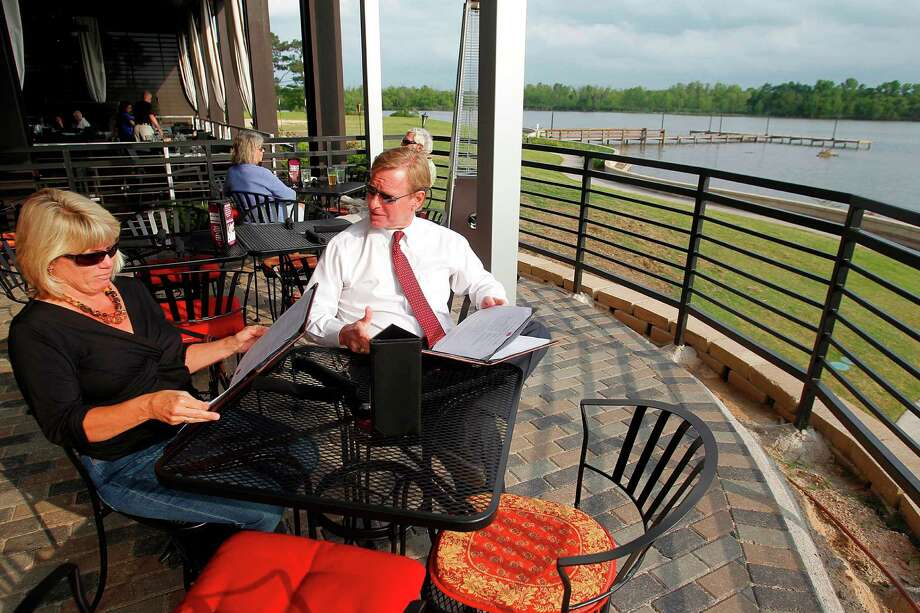 Judy Hammond and husband John Hammond enjoy the breeze, sun, and view of Lake Houston as they dine at The Tasting Room on Wednesday, April 4, 2012, in Kingwood. ( Mayra Beltran / Houston Chronicle ) Photo: Mayra Beltran / © 2012 Houston Chronicle