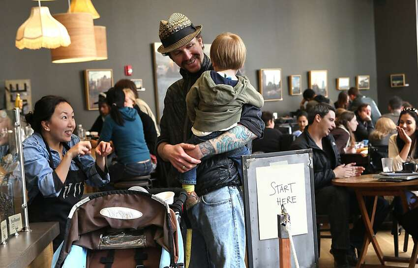 Cortt Dunlap,(middle) managing partner of Awaken Cafe, which opened two months ago in Oakland, Calif., as he is about to leave with his son Keaton Dunlap, 21 mos. old, on Tuesday, April 10, 2012.