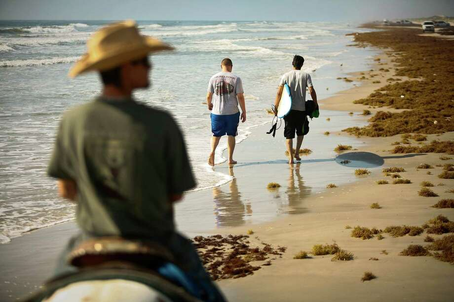 Trail guide Ray Maddox, left, with Horses on the Beach horseback riding company, leads a group of riders past a pair of surfers during a morning ride on North Padre Island in Corpus Christi. The local company offers rides every day of the week, weather permitting. Photo: Nick De La Torre / © 2012  Houston Chronicle