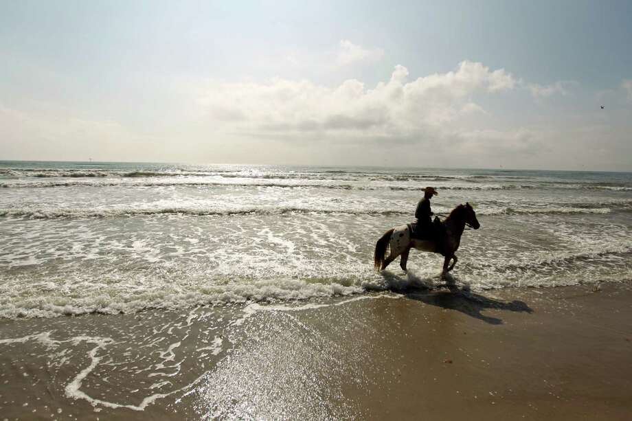Ray Maddox, a horseman with Horses on the Beach, left, lets his horse walk into water as he leads a group of riders on a horseback ride on the beach on Padre Island in Corpus Christi.  Photo: Nick De La Torre / © 2012  Houston Chronicle