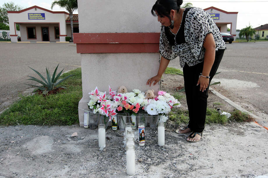 Lucy Moreno, 33, places stuffed bears on a memorial set up at the site of a one-vehicle crash that killed nine immigrants in Palmview, Texas, Wednesday, April 11, 2012. Moreno is an employee at Kids Rock Learning Academy which sits across the street from where the accident occurred. The immigrants were killed in the single vehicle accident late Tuesday night. The accident occurred a few block from where U.S. Border Patrol units attempted to stop the vehicle. Six other passengers in the van were injured. Photo: Jerry Lara, San Antonio Express-News / © San Antonio Express-News