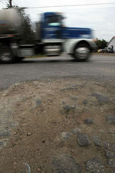 A tanker truck rolls past crumbling asphalt Thursday November 17, 2011 at the intersection of State Highway 119 and State Highway 72 in Yorktown, Texas. The town is in the oil rich Eagle Ford shale formation area where drilling is increasing and the enormous amount ot truck traffic is taking its toll on roads there. JOHN DAVENPORT/jdavenport@express-news.net Photo: JOHN DAVENPORT, SAN ANTONIO EXPRESS-NEWS / SAN ANTONIO EXPRESS-NEWS (Photo can be sold to the public)