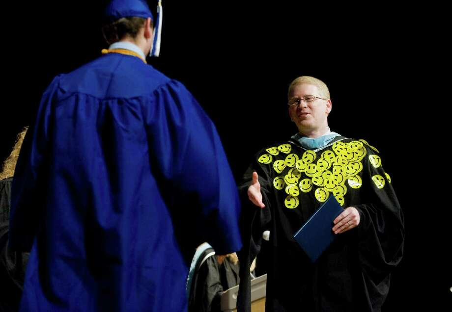 Darien High School Principal Dan Haron announced Wednesday, April 12, 2012, that he will step down at the end of the school year.  The Darien High School Class of 2011 placed happy face stickers on Haron, above, at the Commencement Exercises in Darien, Conn. on June 17, 2011. Photo: File Photo, ST / Stamford Advocate