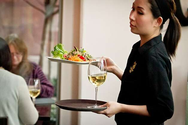 A server carries a salad and a glass of white wine to a table at Kacha Thai Bistro in Walnut Creek, Calif., on Friday April 7th, 2012. Photo: John Storey