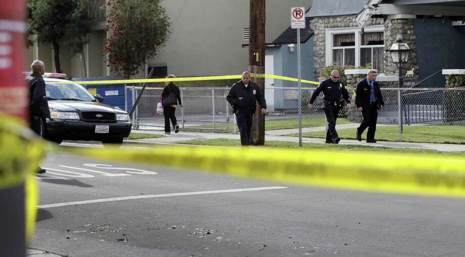 Los Angeles Police Department officers investigate a shooting Wednesday of two USC students in Los Angeles. A search is on for the gunman. Photo: Damian Dovarganes / AP