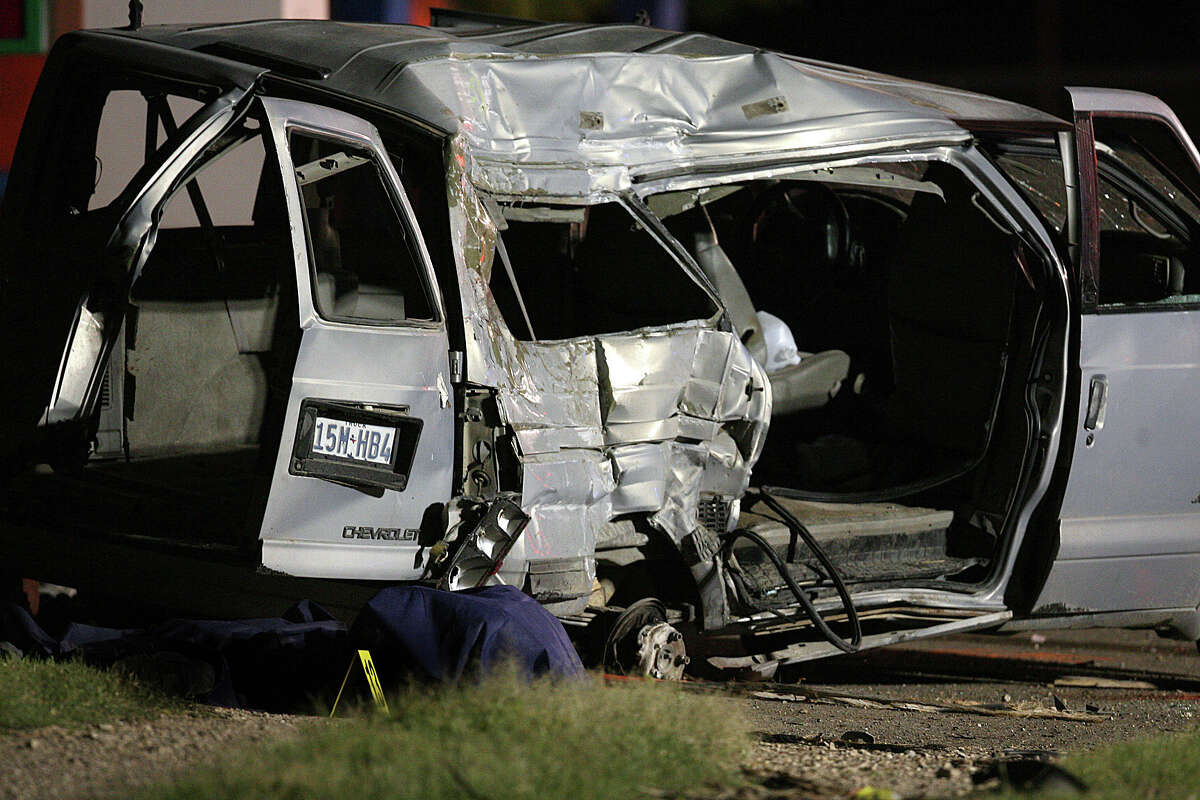 A covered body of a victim lays beside a mini van on Wednesday, April 11, 2012, at the scene of Tuesday's deadly wreck involving a van carrying suspected illegal immigrants in Palmview, Texas. At least nine people were killed and six were hurt in the crash.