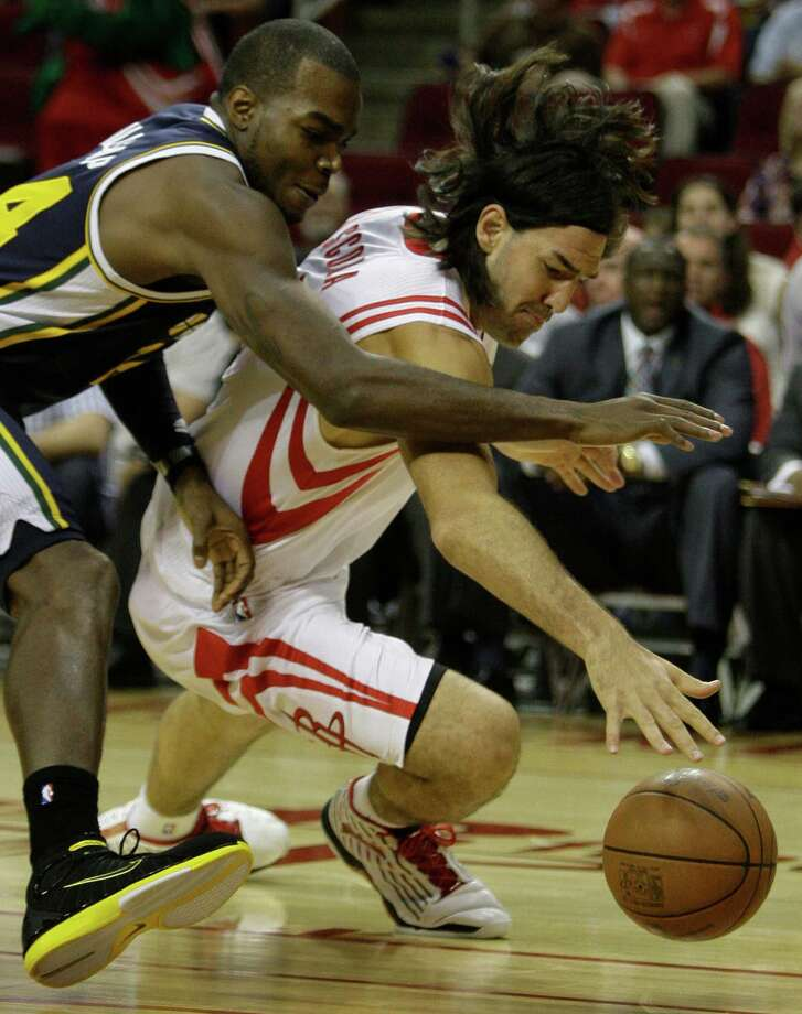 Utah Jazz's Paul Millsap, left,  and Houston Rockets' Luis Scola, right,  scramble to the floor after the ball during the first quarter of NBA game at Toyota Center  Wednesday, April 11, 2012, in Houston. Photo: Melissa Phillip, Houston Chronicle / © 2012 Houston Chronicle