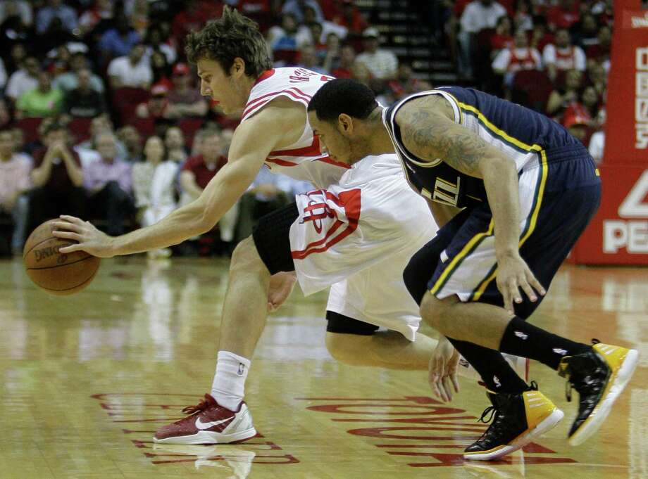 Houston Rockets' Goran Dragic, left, tries to control ball after Utah Jazz's Devin Harris, right, knocked it from him during the first quarter of NBA game at Toyota Center  Wednesday, April 11, 2012, in Houston. Photo: Melissa Phillip, Houston Chronicle / © 2012 Houston Chronicle