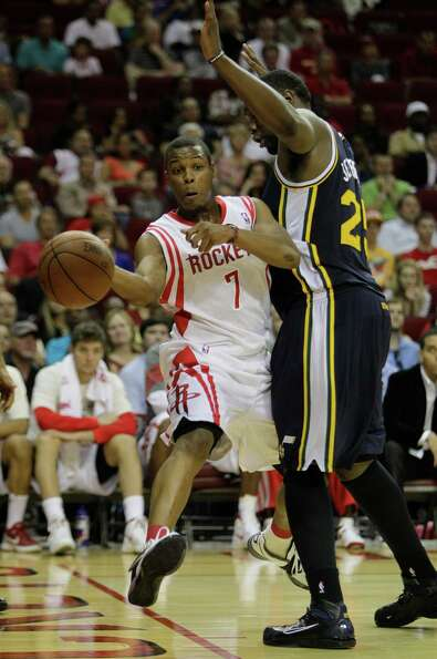 Houston Rockets' Kyle Lowry, left,  passes the ball around Utah Jazz's Al Jefferson, right, during t