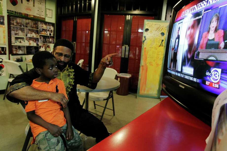 Deloyd Parker tells Lee Rhyne about Trayvon Martin as they watch Wednesday's press conference at the Vegan Cafe in Houston's SHAPE Community Center. Photo: Mayra Beltran / © 2012 Houston Chronicle