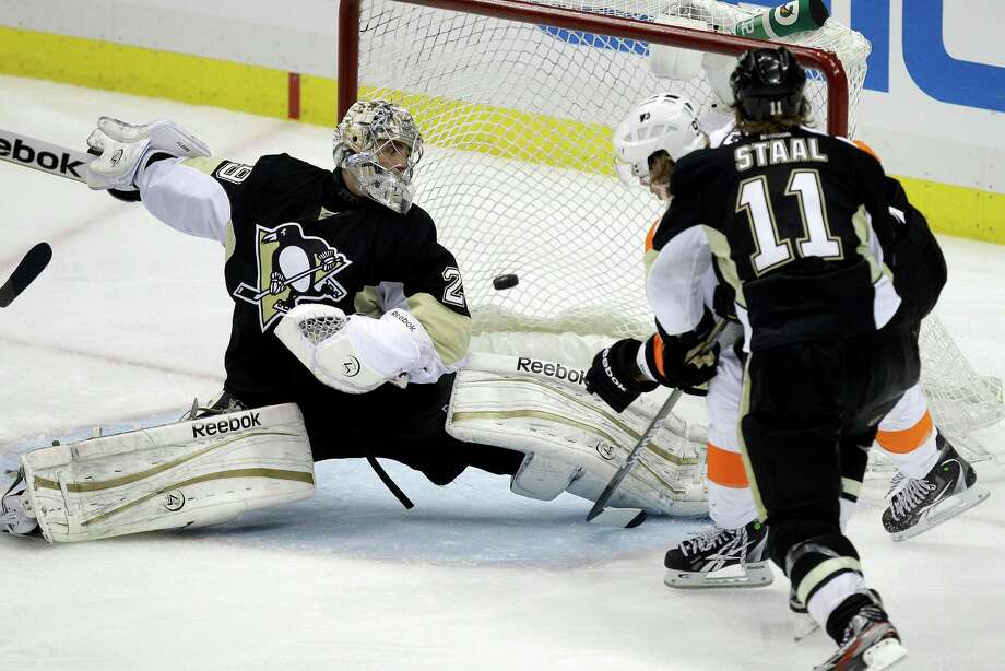 Philadelphia Flyers' Jakub Voracek, right rear, scores a goal in overtime past Pittsburgh Penguins goalie Marc-Andre Fleury (29) and Penguins' Jordan Staal (11) during Game 1 of the opening-round NHL hockey playoff series Wednesday, April 11, 2012, in Pittsburgh. The Flyers won 4-3. (AP Photo/Gene J. Puskar) Photo: Gene J. Puskar / AP