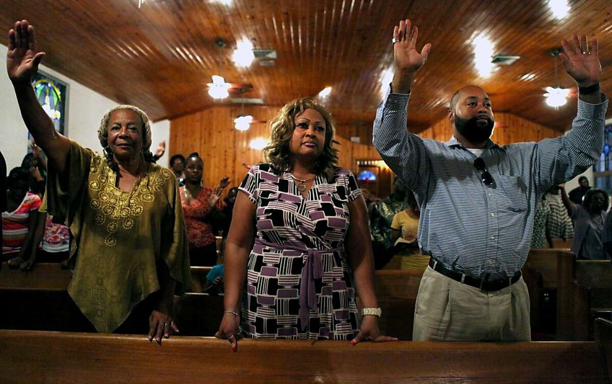 Francis Oliver, left, Dr. Cappila Gaines, center, and Kelly Gaines, right, react to the news of George Zimmerman's arrest at the Allen Chapel in Sanford, Fla.,Wednesday, April 11, 2012. Zimmerman, 28, the neighborhood watch volunteer who shot Trayvon Martin, 17, was arrested and charged with second-degree murder Wednesday after weeks of mounting tensions and protests across the U.S. Zimmerman could get up to life in prison if convicted in the slaying of the unarmed black teenager. (AP Photo/Julie Fletcher)