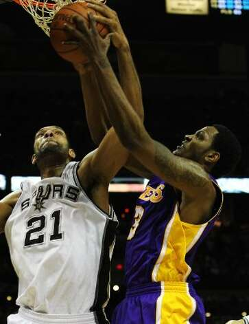Spurs' Tim Duncan (21) fights for a rebound with Los Angeles Lakers' Devin Ebanks (03) in the first half at the AT&T Center on Wednesday, Apr. 11, 2012. Kin Man Hui/Express-News. (San Antonio Express-News)