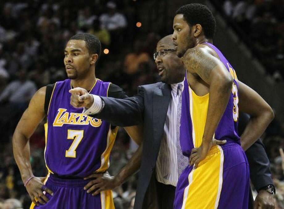 Los Angeles Lakers coach Mike Brown (center) talks to his players Ramon Sessions (07) and Devin Ebanks (03) during a pause in the game against the Spurs in the first half at the AT&T Center on Wednesday, Apr. 11, 2012. Kin Man Hui/Express-News. (San Antonio Express-News)