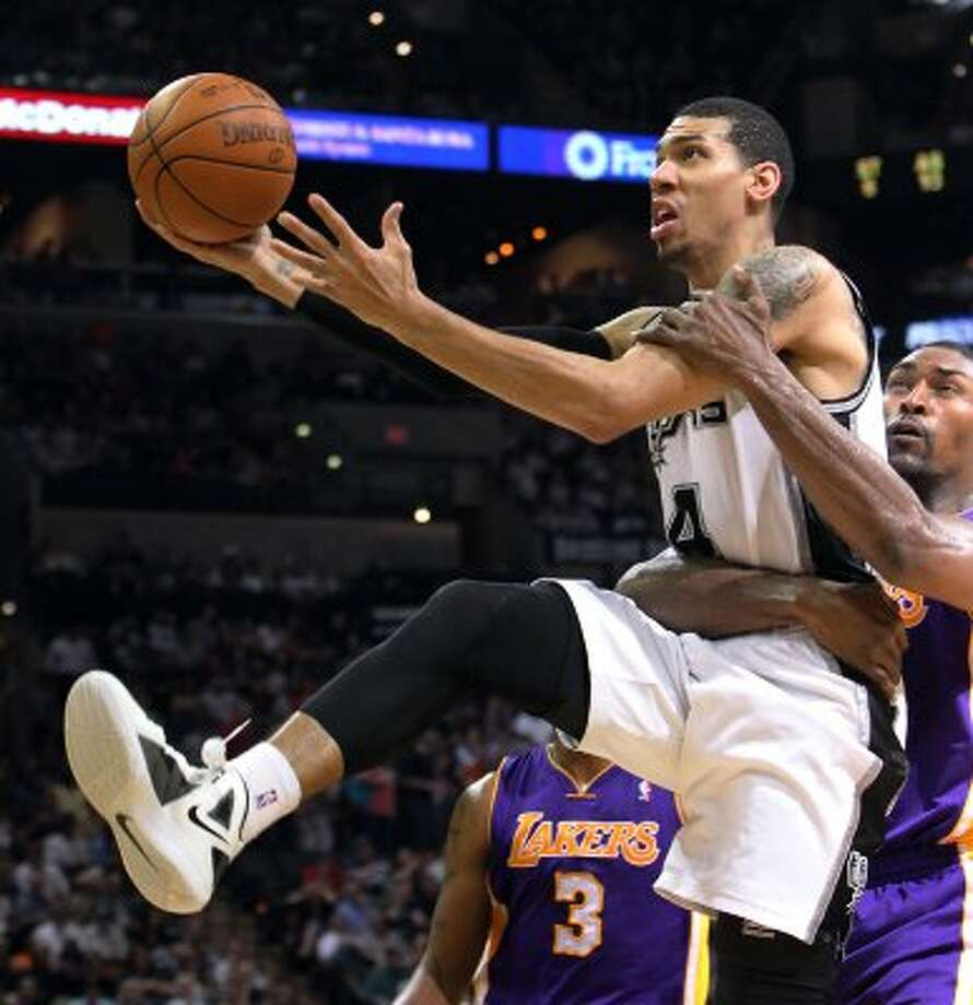 Spurs' Danny Green (04) takes a hard foul by Los Angeles Lakers' Metta World Peace (15) in the second half at the AT&T Center on Wednesday, Apr. 11, 2012. Spurs lose to the Lakers, 84-98. Kin Man Hui/Express-News. (San Antonio Express-News)
