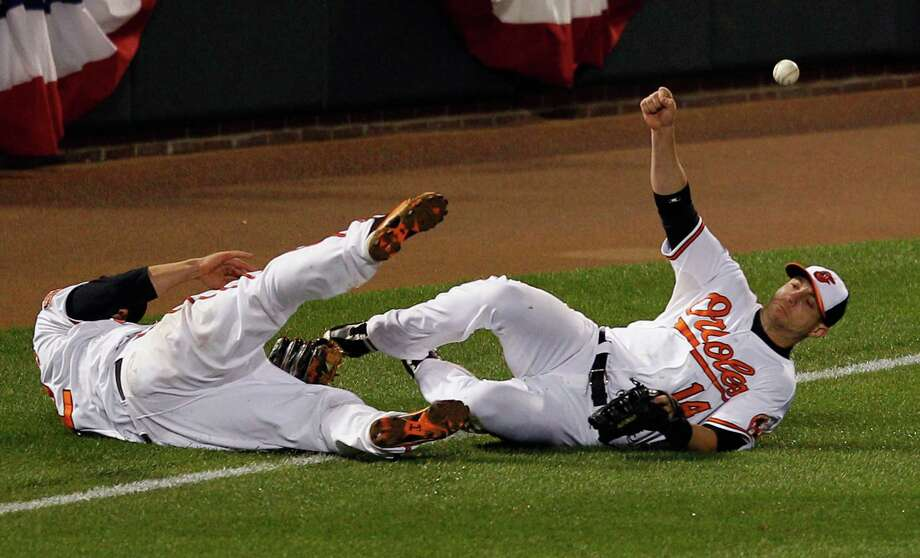 The Orioles' Mark Reynolds, left, and Nolan Reimold fail to corral a ball hit by Mark Teixeira, prolonging the 10th inning long enough for Nick Swisher to homer. Photo: Rob Carr / 2012 Getty Images
