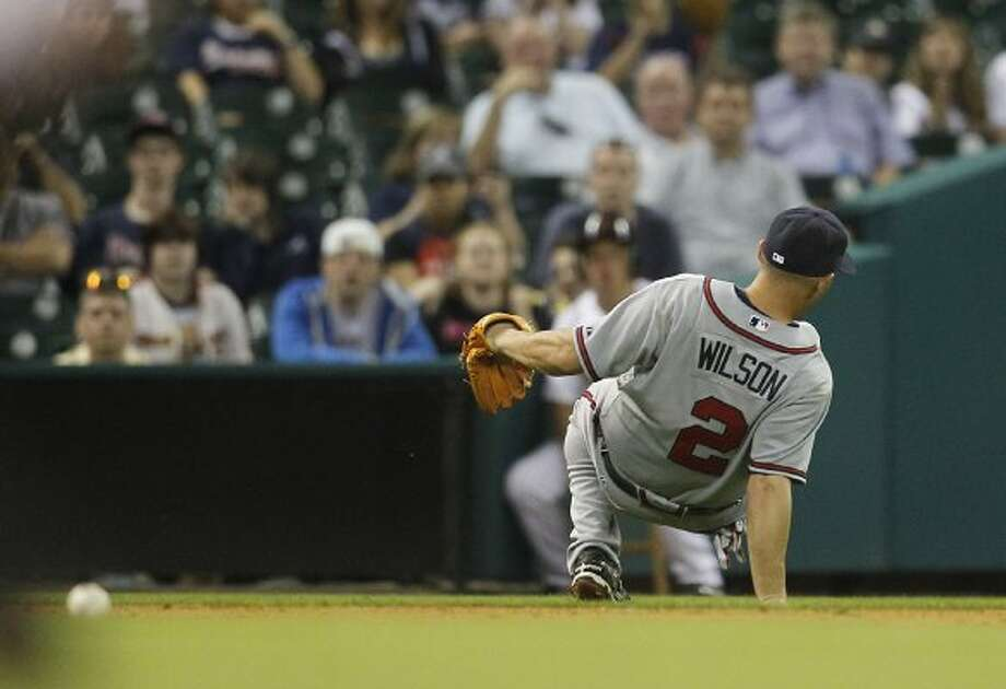 Braves shortstop Jack Wilson falls over backward as he chases a ball hit by Chris Johnson during the eighth inning. (Karen Warren / Houston Chronicle)