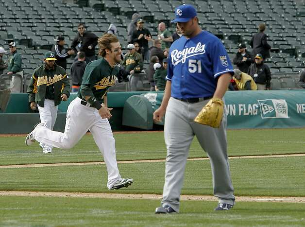 Oakland's Collin Cowgill races past Royals pitcher, Jonathan Broxton as he celebrates the teams victory in the 12th inning, after Broxton hit two batters to walk in the final winning run for Oaklad, as the Athletics beat the Kansas City Royals 5-4, in major league baseball action at the O.Co Coliseum on Wednesday April 11, 2012, in Oakland, Ca. Photo: Michael Macor, The Chronicle