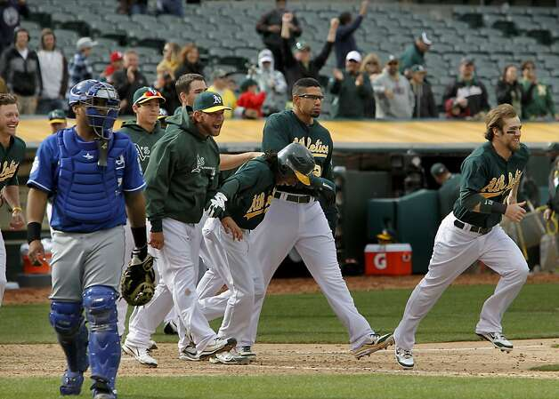 The Athletics celebrate after Oakland's Jonny Gomes was hit by a pitch with the bases loaded in the 12th inning to give the team the victory 5-4,  as Oakland beat the Kansas City Royals in major league baseball action at the O.Co Coliseum on Wednesday April 11, 2012, in Oakland, Ca. Photo: Michael Macor, The Chronicle
