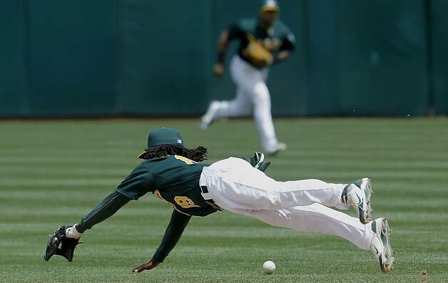 Oakland's Jemile Weeks dives for but can't reach a single hit by Alex Gordon in the third inning, as the Oakland Athletics went on to bet the Kansas City Royals 5-4, in major league baseball action at the O.Co Coliseum on Wednesday April 11, 2012, in Oakland, Ca. Photo: Michael Macor, The Chronicle