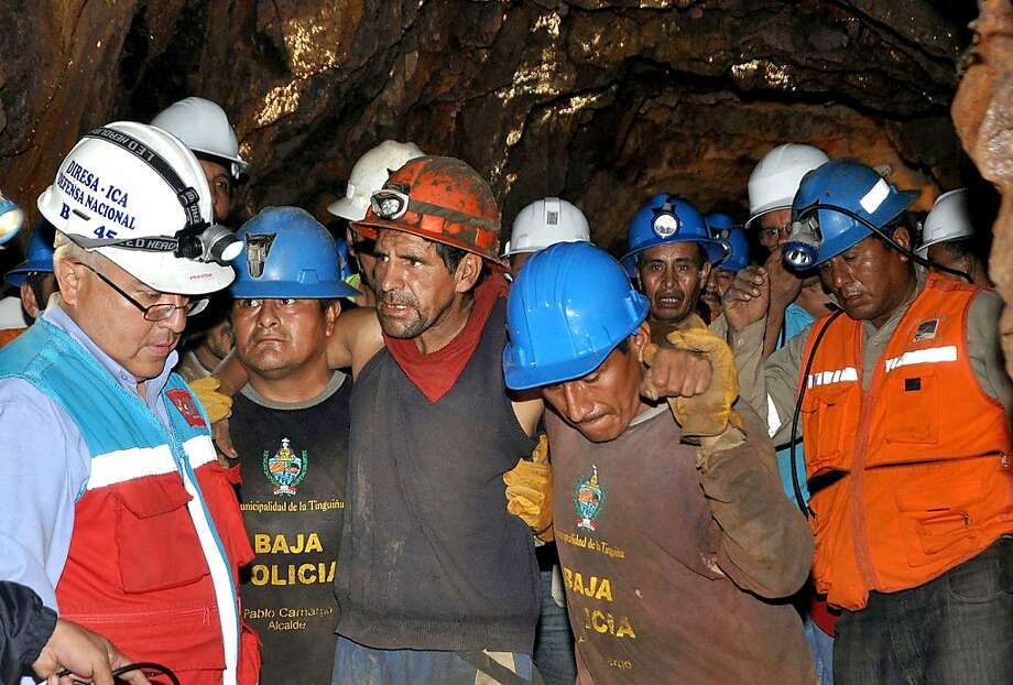 Rescued miners are ushered out of the Cabeza de Negro mine on April 11, 2012, after being trapped 250 meters underground for seven days, 1300 meters above sea level in the Andes east of Ica, 325 km south of Lima. President Ollanta Humala directed the final stage of the operation, which lead to the rescue of nine trapped miners. Photo: Andina, AFP/Getty Images