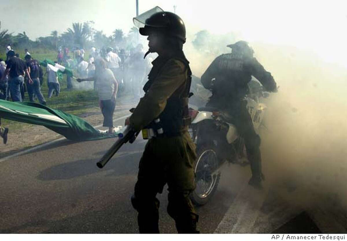 Riot police disperse demonstrators at the Viru Viru international airport in Santa Cruz de la Sierra, Bolivia, Thursday, Oct. 18, 2007. Soldiers and police officers fired tear gas at angry residents who attempted to storm Bolivia's busiest airport as the facility became a focal point of an autonomy dispute between the federal government and the country's wealthiest province. (AP Photo/Amanecer Tedesqui) EFE OUT