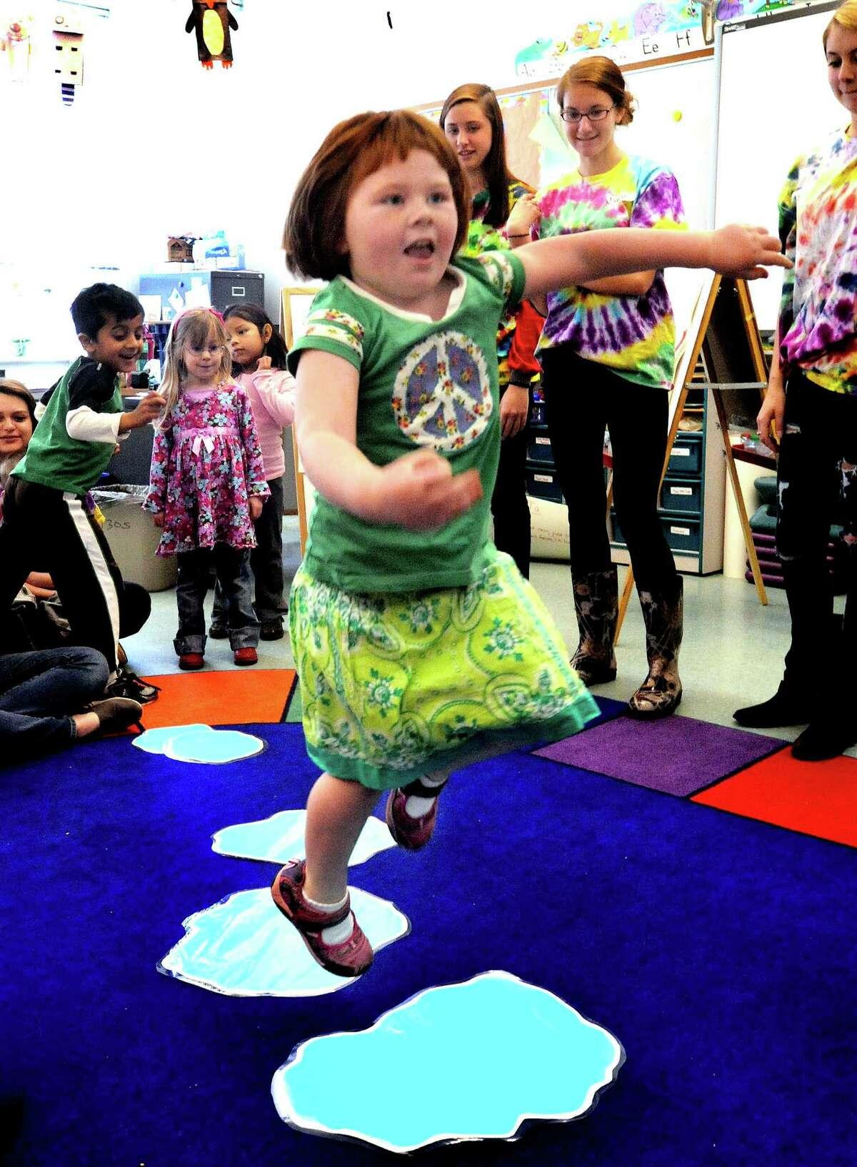Emma Kavaneah, 5, jumps puddles during a child development class at New Milford High School Thursday, April 12, 2012.