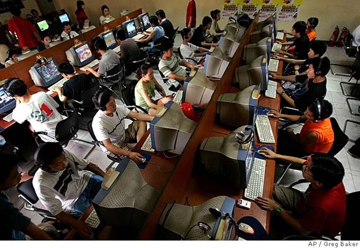 ** FILE ** Chinese youth use computers at an Internet cafe in Beijing in this June 18, 2005 file photo. Internet companies that face hearings Wednesday before angry U.S. lawmakers say they can't resist China's effort to censor the Web on their own. But industry analysts say that even if Washington tried to enforce free-speech standards, it is likely to have little effect. (AP Photo/Greg Baker, File)