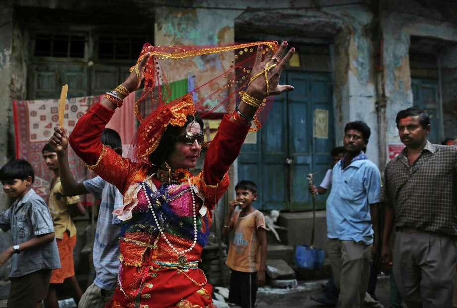 An Indian transgender Hindu devotee dances while marking the festival of Shiva Gajan in the city of Kolkata, in West Bengal, India, Thursday, April 12, 2012. The celebrations mark the final days of the Bengali calendar. (AP Photo/Kevin Frayer) Photo: Kevin Frayer, Associated Press / AP