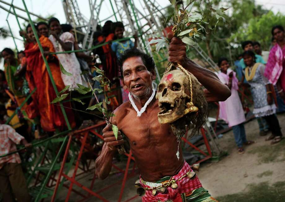 An Indian Hindu devotee dances while carrying a human skull during a brief ceremony marking Shiva Gajan, in Burdwan district, east of Kokata,in West Bengal, India, Thursday, April 12, 2012. The skulls are dug up from un-marked graves and carried around by a small group of followers as an offering for Lord Shiva during celebrations marking the final days of the Bengali calendar. (AP Photo/Kevin Frayer) Photo: Kevin Frayer, Associated Press / AP