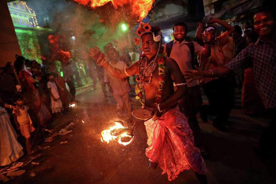 An Indian Hindu devotee dances around with a burning torch while marking the festival of Shiva Gajan in the city of Kolkata, in West Bengal, India, Thursday, April 12, 2012. The celebrations mark the final days of the Bengali calendar. (AP Photo/Kevin Frayer) Photo: Kevin Frayer, Associated Press / AP
