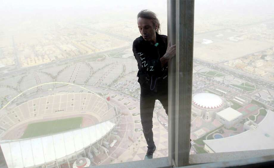 Alain Robert, who has been dubbed the 'French Spiderman', climbs 300 meters up The Torch hotel in Doha on April 12, 2012. Robert, who has been scaling tall buildings since the age of seven took 75 minutes to complete his first climb in Qatar of the hotel that was built for the 2006 Asian Games in the shape of an Olympic torch. AFP PHOTO/FAISAL AL-TAMIMI Photo: FAISAL AL-TAMIMI, AFP/Getty Images / AFP