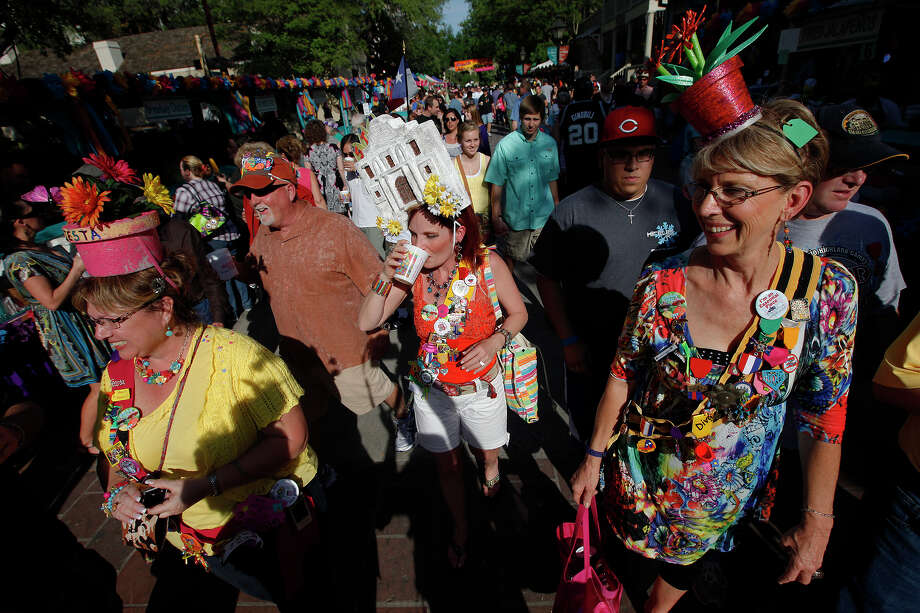 Members of the Fiesta Hat Queens Diana Eberhard (from left), Brian Lindsey, Joy Lindsey and Jackie Mitchell stroll down the main strip of La Villita during the opening of Night in Old San Antonio (NIOSA) on Tuesday, April 12, 2011. Each year throngs of people flock to the narrow alleys of the square to enjoy food and beverages. Lindsey (center) said she made her hat in honor of the 175th anniversary of the battle at the Alamo for this year's NIOSA celebrations. Kin Man Hui/kmhui@express-news.net Photo: KIN MAN HUI, SAN ANTONIO EXPRESS-NEWS / San Antonio Express-News