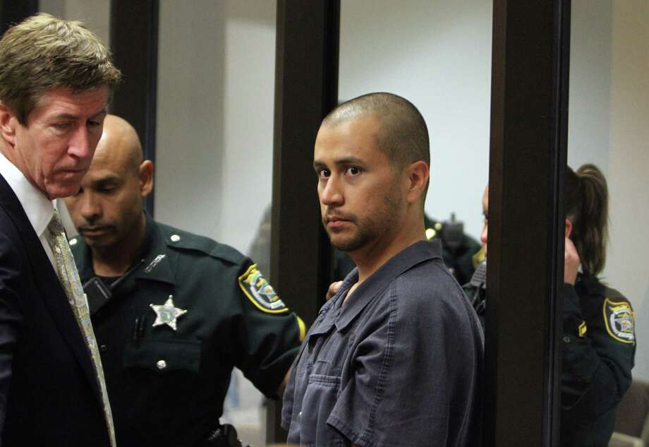 George Zimmerman, center, is directed by a Seminole County Deputy and his attorney Mark O'Mara during a court hearing Thursday April 12, 2012, in Sanford, Fla.  Zimmerman has been charged with second-degree murder in the shooting death of the 17-year-old Trayvon Martin. (AP Photo/Gary W. Green, Orlando Sentinel, Pool) Photo: Gary W. Green, POOL / Pool Orlando Sentinel